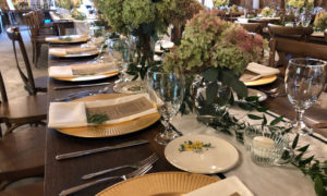 Rustic Wooden Tables Set With Rustic Dinnerware at a Wedding Reception