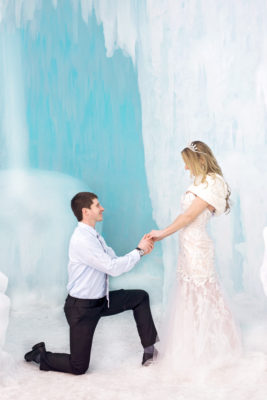 Groom to Be Proposing to His Bride To Be while she wears a white dress with a real iceberg background