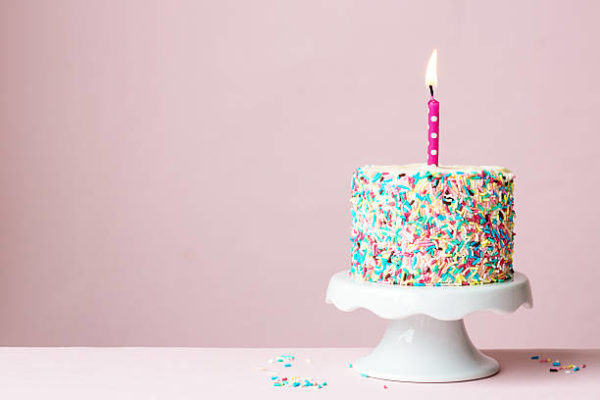 Colorful birthday cake with one candle lit on a pink background