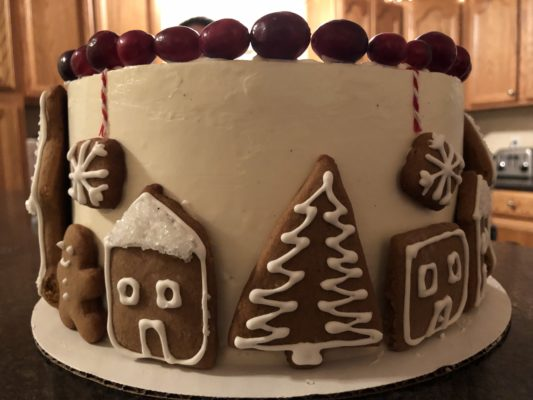 Vanilla Spice 8 inch holiday cake with white frosting, gingerbread cookies, and cranberry garnish