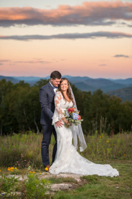 Bride and Groom posing in the sunset on top of a mountain at Sunday River