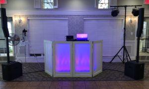 Wedding DJ Setup with white facade backlit with purple lighting.