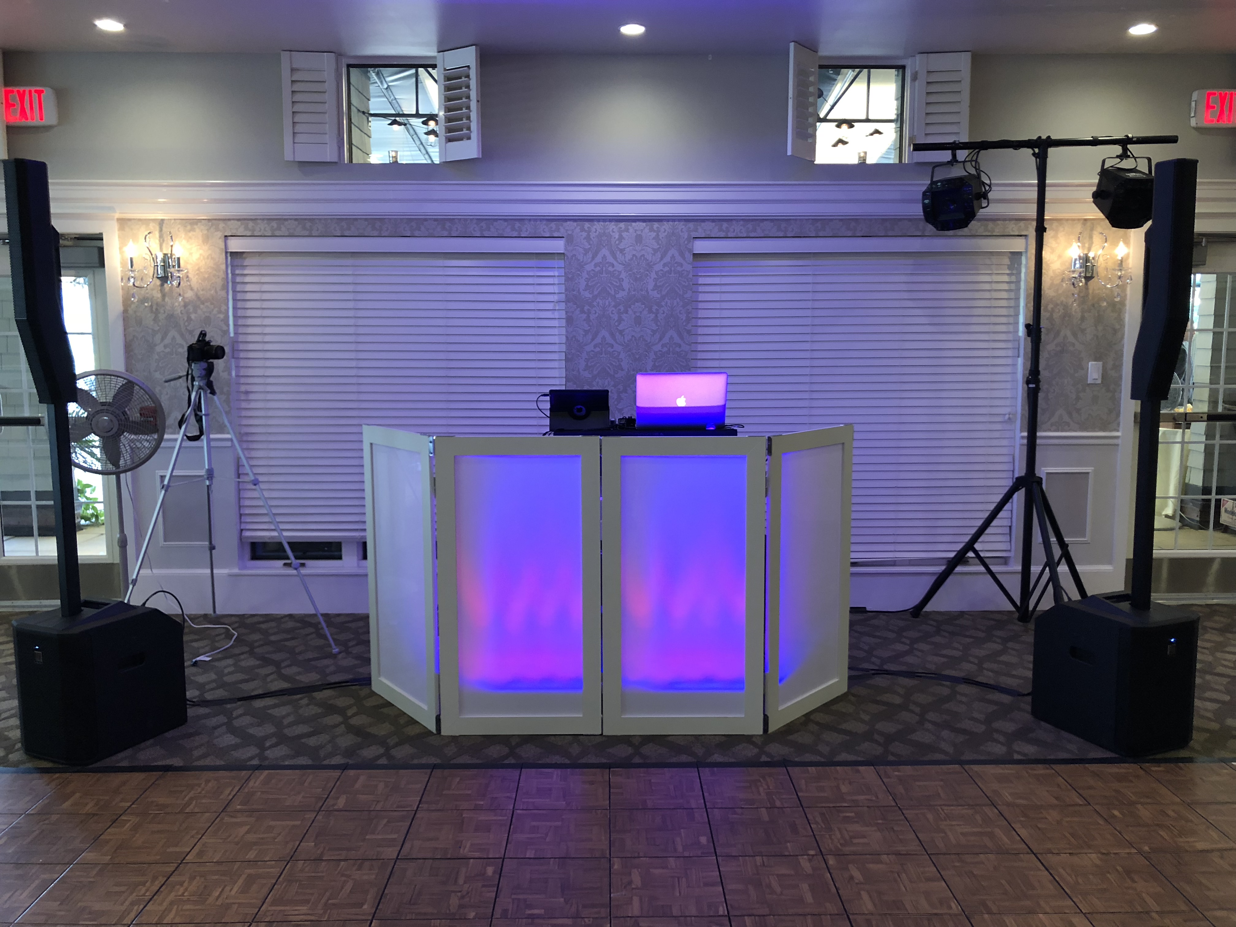 Wedding DJ Setup with white facade backlit with purple lighting.