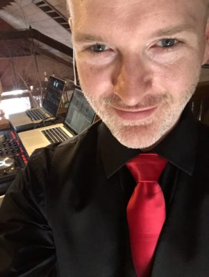 DJ Chris Bouchard of Bouchard Entertainment in a black suit with red tie