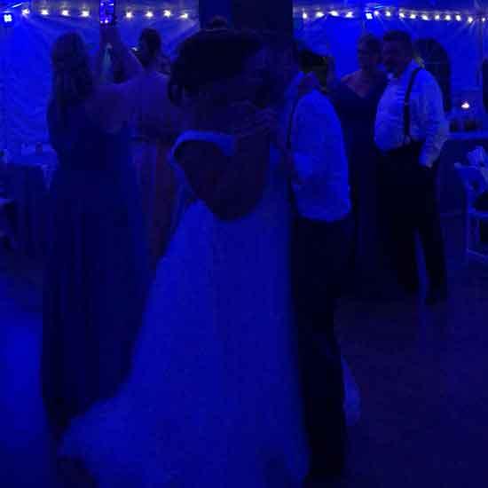 bride and groom dancing under blue tent uplighting